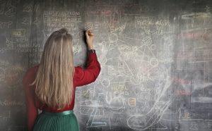 a woman writing on a chalk board