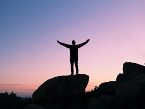 a silhouette of man raising his hands out of gratitude