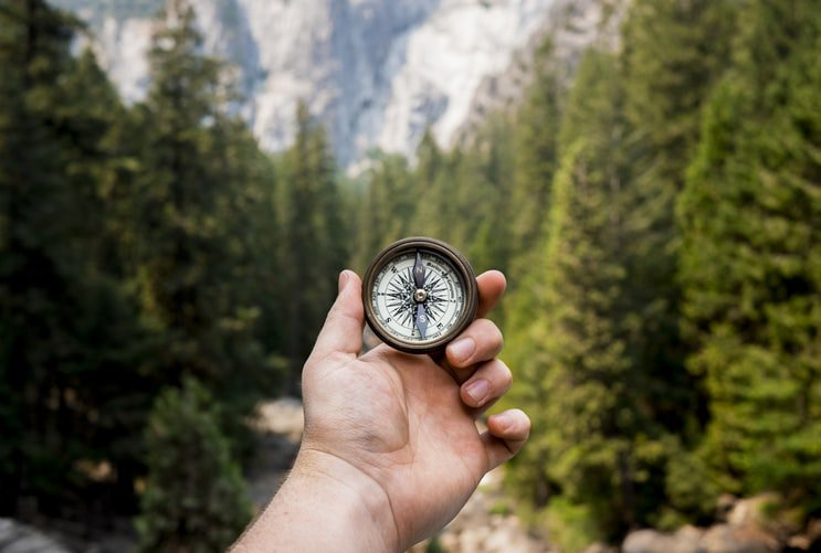 Person holding compass on mountain trail