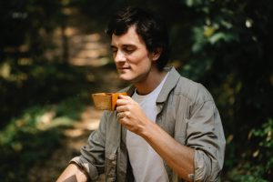 A man is mindfully drinking a cup of coffee