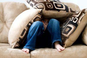a child hiding under pillows